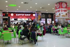 Russia, Novosibirsk, January 7, 2019: visitors girls Burger king eat at a fast food table waiting for the order stock photography