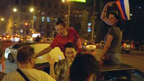 Girls from car give five crowd celebrates victory of football match. Russia, Novosibirsk, July 2, 2018: Victory of Russia in a football match. In night city stock video