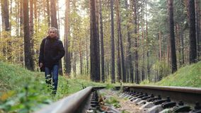 Russia, Novosibirsk, 5 october 2016, Alone man walking on Railway Road in the deep pine forest. 3840x2160. Railway Road in the pine forest stock video