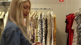 Russia, Novosibirsk, October 2019. Young attractive blonde is happy to shop in a clothing store stock video footage