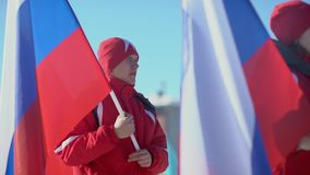 Russia, Novosibirsk, 2016: Opening of sports competitions. Winter sports. Russia, Novosibirsk, 2016: Athletes in winter clothes carry the Russian flag. Column stock video footage