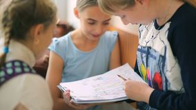 Russia, Novosibirsk, 2015: Schoolgirls communicate. Classmates. Russia, Novosibirsk, 2015: Schoolgirls communicate. Three schoolgirls are considering drawing stock footage