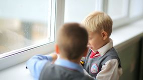 Russia, Novosibirsk, 2015: Two boys in a school uniform playing. Elementary-school. Boy with white hair in school uniform playing with a toy car. School stock footage