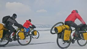 RUSSIA, OLKHON - FEBRUARY 28, 2018: Cyclists travelers from Poland ride ice on bicycles. Extremes cross Lake Baikal. Along its length. Route of the hike is more stock video footage