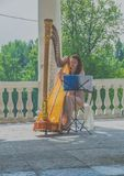 Russia, Pavlovsk Park, July 22, 2017 at a flower festival in the. Russia, Pavlovsk Park, July 22, 2017 girl harpist performs at the festival of flowers Royalty Free Stock Image