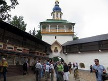 Russia. Pechora. Pskov Caves Monastery. Russia. Pskov. 2013, August 09. Pskov Caves Monastery. View of main entrance and people coming in monastery yard Stock Photos