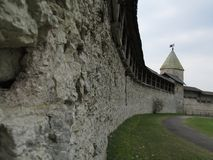 Russia, Pskov, Pskov Kremlin in early spring. Russia. Pskov.The Pskov Kremlin, a fortified wall and watchtower. Early spring. Dull cloudy weather Royalty Free Stock Photo