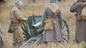 RUSSIA, REPUBLIC OF TATARSTAN 30-09-2019: A reconstruction of military operations in Russia in 1917 - Soldiers setting. The cannon gun in place on the stock footage