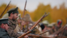 RUSSIA, REPUBLIC OF TATARSTAN 30-09-2019: A reconstruction of military operations in Russia in 1917 - Soldiers standing. In the row and putting their guns up stock video