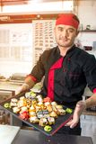Russia, Ryazan - 12.11.2018 - Smiling asian chef with sushi on kitchen royalty free stock images