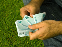 Russia's money. The hands against the backdrop of green grass Russia money Stock Images