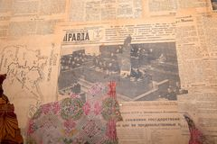 Old newspaper Pravda. RUSSIA, SAINT PETERSBURG - AUGUST 18, 2017: Fragment of an old wall with ragged wallpaper and old communist newspapers Royalty Free Stock Photo