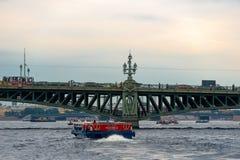 Under the Trinity Bridge. RUSSIA, SAINT PETERSBURG - AUGUST 18, 2017: Pleasure excursion boat with tourists walking along the Neva River under the Trinity Bridge Stock Photo