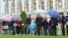 RUSSIA, SAINT PETERSBURG, 20 june 2017, Crowd of people under umbrellas covers in pouring rain stand in line to the. Crowd of people under umbrellas covers in Stock Images