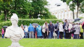 RUSSIA, SAINT PETERSBURG, 20 june 2017, Slow motion crowd of people under umbrellas covers in pouring rain on green. Crowd of people under umbrellas covers in Stock Photos