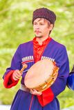 Kazak musician holds a tambourine in his hands and beats him with a beater royalty free stock photos