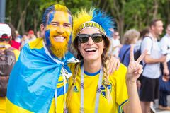 Football fans from Sweden, married couple, with painted faces in national colors before the match England Sweden at the World Cup