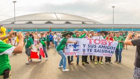 A group of Mexican football fans celebrating the World Cup in football against the backdrop of the Samara Arena stadium. Russia, Samara, June 2018: a group of royalty free stock photo