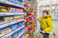 A beautiful mature woman is choosing goodies for her grandchildren in a supermarket. Russia Samara March 2019: A beautiful mature woman is choosing goodies for royalty free stock photography