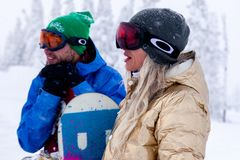 Russia, Sheregesh 2018.11.18 Couple of snowboarders in bright sp royalty free stock photo