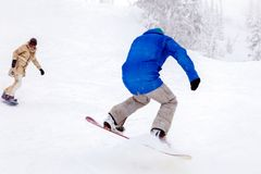 Russia, Sheregesh 2018.11.18 Couple of snowboarders in bright sp stock photography