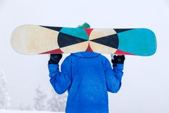 Russia, Sheregesh 2018.11.18 Professional man snowboarder in bright blue sportswear and outfit in snowy sunny high mountains. Con royalty free stock images