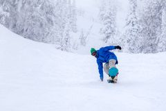 Russia, Sheregesh 2018.11.18 Professional man snowboarder in bright sportswear and outfit skiing downhill in snowy sunny high royalty free stock photo