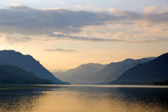 Russia. Siberia. Altai. Mirror of Teletskoye lake. Early in the morning. Orange sky reflecting in the calm water stock images
