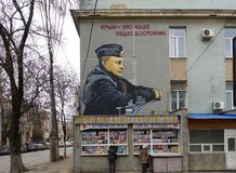 Russia, Simferopol. 2019 January 01: Color graffiti portrait of Russian President Vladimir Putin on a street wall in military. Uniform stock photo