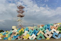 Navigation tower of Adler sea port over bright concrete protective structures. Cloudy day in early summer Royalty Free Stock Photo