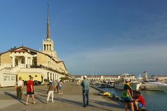 Tourists near the building of the seaport of Sochi. Warm summer evening Royalty Free Stock Photo