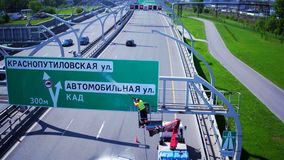 RUSSIA ST.PETERBURG- 28 MAY 2016: Aerial view of worker on industrial crane clean road sign with pressurized water, wet stock video footage