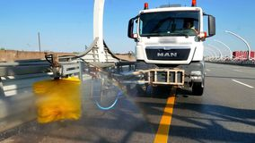 RUSSIA ST.PETERBURG- 28 MAY 2016: city road cleaning machine clearing road barriers in modern highway with water jet and stock footage