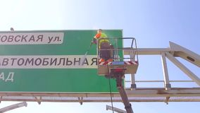 RUSSIA ST.PETERBURG- 28 MAY 2016: worker on industrial crane clean road sign with pressurized water, wet cleaning of stock video