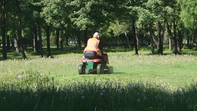 Russia, St. Petersburg, June 4, 2019 - the working on a tractor lawn mower in the Park mowing grass stock footage
