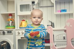 Russia. St. Petersburg. March 19, 2019. A small child plays in the children`s kitchen. one year old boy with pleasure stock photo