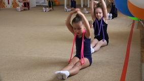 Small athletes perform gymnastic exercises on the carpet stock video footage