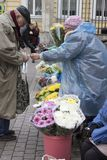 Russia. St. Petersburg. Street market at the metro station. The old man buys flowers on the street market royalty free stock images