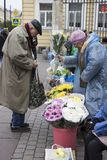 Russia. St. Petersburg. Street market at the metro station. The old man buys flowers on the street market royalty free stock photo