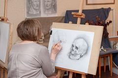 An adult female student sits at the easel, learning to draw stock image