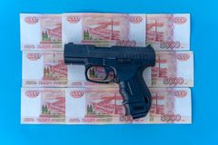 Close up image of pistol and rubles money. Walter and rubles on a blue background close-up stock images