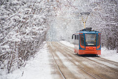 Russian tram on park. Russian tram moves on rails in park winter stock photography