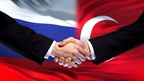 Russia and Turkey handshake, international friendship relations, flag background. Stock photo royalty free stock photography