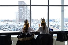 Russia, Tyumen, 30.03.2019. Teenage girls in crowns from Burger king for lunch at the Mall. Girls eat in the shopping center. Rear stock photos