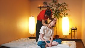 RUSSIA, Ufa - APRIL 06, 2018: Caucasian girl with long hair stretching her body with Thai masseur stock video