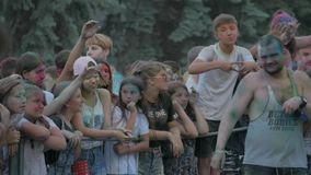 RUSSIA, URYUPINSK - JUNE 29, 2018: Crowd of people colored powder and having fun. Color powder relaxing at outdoor party stock video footage