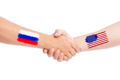 Russia and USA hands shaking with flags Stock Photos