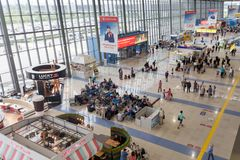 Interior view of Vladivostok International Airport. Many passengers waiting for boarding, cafe and stores stock photography