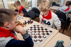 Russia, Vladivostok, 12/01/2018. Kids play chess during chess competition in chess club. Education, chess and mind games. stock image
