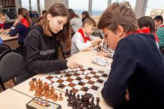 Russia, Vladivostok, 12/01/2018. Kids play chess during chess competition in chess club. Education, chess and mind games. stock photography